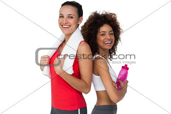 Fit young women standing with waterbottle and towel