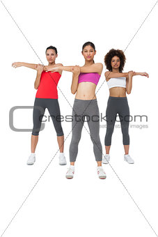 Three sporty young women stretching hands