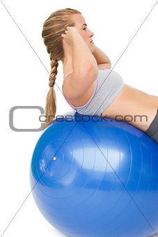 Fit young woman doing crunches on exercise ball