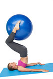 Side view of a fit woman exercising with fitness ball