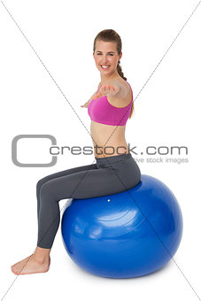 Fit young woman exercising on fitness ball