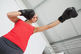 Determined female boxer focused on training at gym