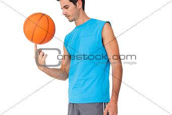 Basketball player holding ball on finger