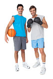 Two fit men with boxing gloves and basketball