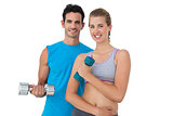 Portrait of a fit couple exercising with dumbbells