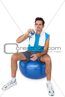 Fit man sitting on exercise ball while drinking water