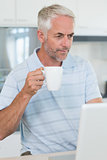 Casual man looking at his laptop while having coffee