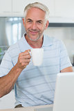Smiling man using his laptop while having coffee
