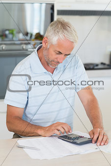 Focused man figuring out his finances