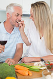 Affectionate couple preparing dinner together and drinking red wine