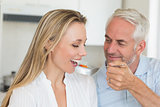 Happy man feeding his partner a spoon of vegetables
