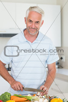 Casual man slicing vegetables and smiling at camera