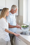 Couple rinsing vegetables at the sink