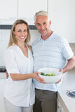 Couple holding bowl of broccoli smiling at camera