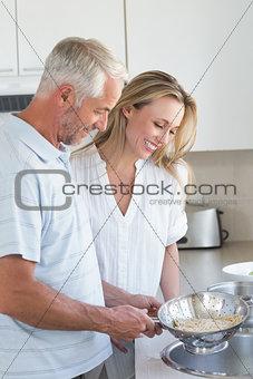 Couple draining spaghetti in colander