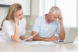 Worried couple working out their finances with laptop