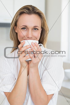 Smiling woman sitting and holding mug