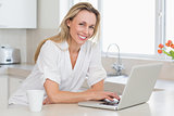 Happy woman using laptop at counter