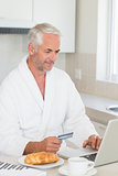 Happy man shopping online at breakfast in a bathrobe