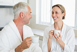 Smiling couple having coffee at breakfast in bathrobes