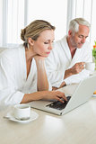 Couple having coffee at breakfast in bathrobes using laptop