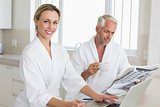 Couple shopping online and reading newspaper in bathrobes