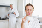 Happy woman drinking coffee in bathrobe