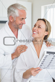 Happy couple reading newspaper together in bathrobes