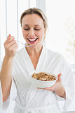 Smiling woman in bathrobe having cereal