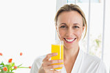 Smiling woman in bathrobe having glass of orange juice
