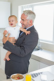 Smiling businessman holding his baby in the morning before work