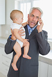 Distracted businessman holding his baby in the morning before work