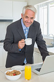 Happy businessman using laptop in the morning before work