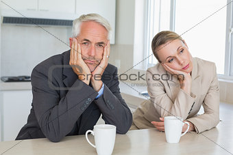 Bored business couple having coffee before work in morning
