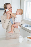 Happy businesswoman holding her baby talking on the phone