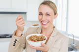 Happy businesswoman eating cereal before work in the morning