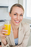 Happy businesswoman having orange juice before work in the morning