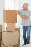Smiling man looking at cardboard moving boxes