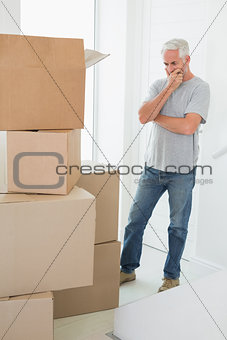 Thoughtful man looking at cardboard moving boxes