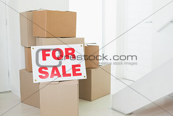 For sale sign with many cardboard boxes