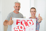 Happy couple standing and holding sold sign giving thumbs up