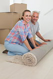 Happy couple rolling out new rug