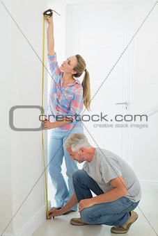 Happy couple making some measurements together