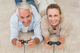 Smiling couple lying on rug playing video games