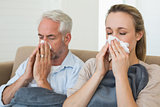 Sick couple blowing their noses sitting on the couch