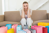 Regretful woman looking at many shopping bags on the couch