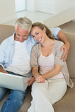 Happy couple using the laptop together on the couch