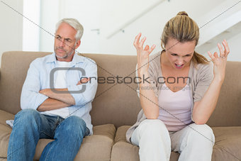 Angry couple sitting on couch arguing