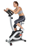 Side view of a beautiful woman on stationary bike