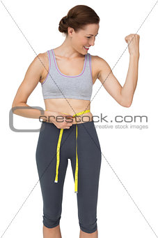 Fit woman measuring waist while flexing muscles